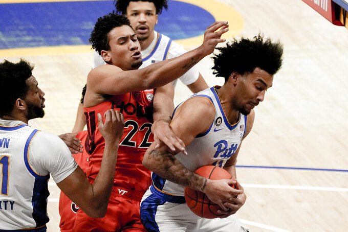 Pittsburgh's Justin Champagnie, right, grabs a rebound in front of Virginia Tech's Keve Aluma (22) during the first half of an NCAA college basketball game Wednesday, Feb. 3, 2021, in Pittsburgh. (AP Photo/Keith Srakocic)