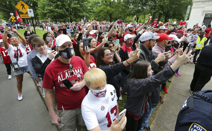 Fans line barricades at the Denny Chimes to watch the Captain's Ceremony where the permanent captains from the 2019 and 2020 teams have their hand and foot prints set in cement at the base of the chimes before for the Crimson Tide's spring NCAA college football game at Bryant-Denny Stadium, Saturday, April 17, 2021, in Tuscaloosa, Ala. (Gary Cosby/The Tuscaloosa News via AP)