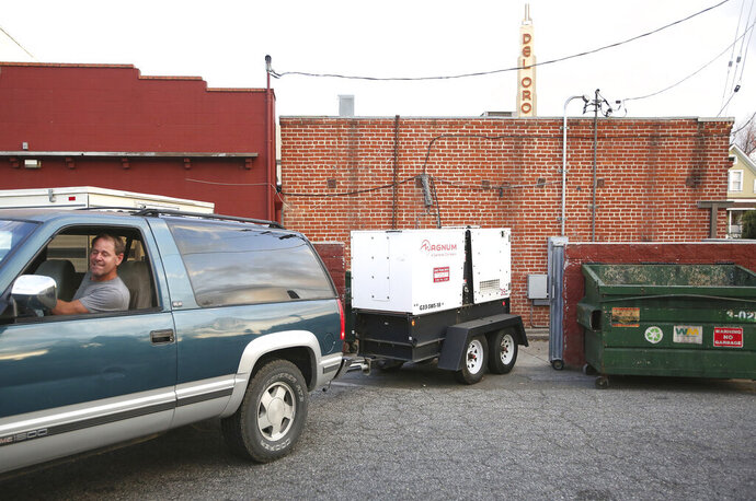 Gary's Place handyman Art Ellis backs an industrial generator into a space behind the downtown Grass Valley bar Tuesday in preparation of a Wednesday and Thursday PG&E power shutdown. (Elias Funez/The Union via AP)