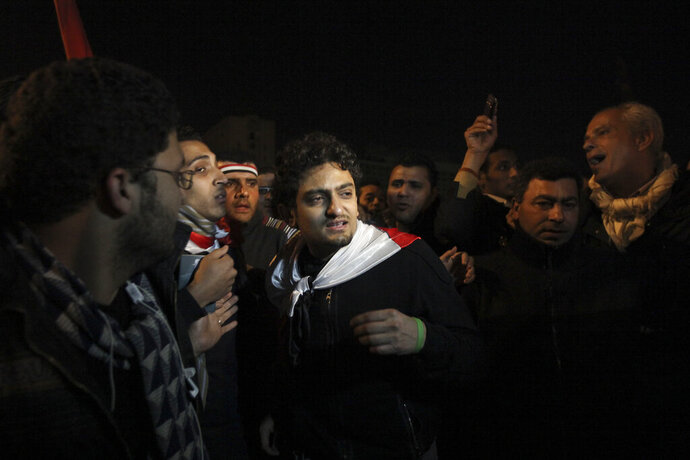 FILE - In this Feb. 10, 2011 file photo, Egyptian Wael Ghonim, center,  walks into Tahrir Square after Egyptian President Hosni Mubarak's televised statement to his nation, in downtown Cairo, Egypt.   Ghonim said late Thursday, Sept. 19, 2019 in a video on his twitter account that authorities raided his parents' house in Cairo and arrested his brother Hazem, whom he described as