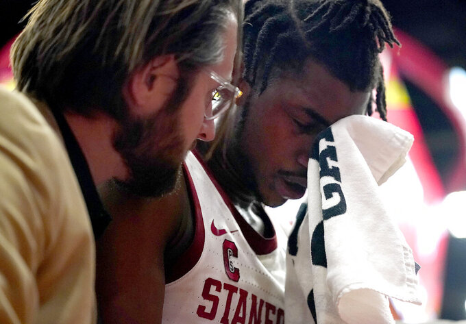 Stanford guard Daejon Davis, right, is taken off the court by a trainer after a collision against Washington during the first half of an NCAA college basketball game Thursday, Jan. 9, 2020, in Stanford, Calif. (AP Photo/Tony Avelar)