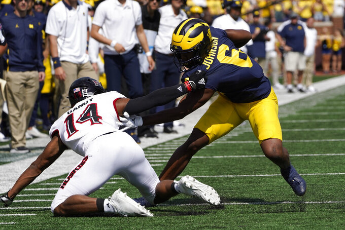 Michigan wide receiver Cornelius Johnson (6) breaks the tackle of Northern Illinois cornerback Jordan Gandy (14) in the first half of a NCAA college football game in Ann Arbor, Mich., Saturday, Sept. 18, 2021. (AP Photo/Paul Sancya)