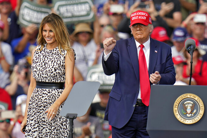President Donald Trump pumps his fist as first lady Melania Trump smiles at supporters after a campaign rally Thursday, Oct. 29, 2020, in Tampa, Fla. (AP Photo/Chris O'Meara)