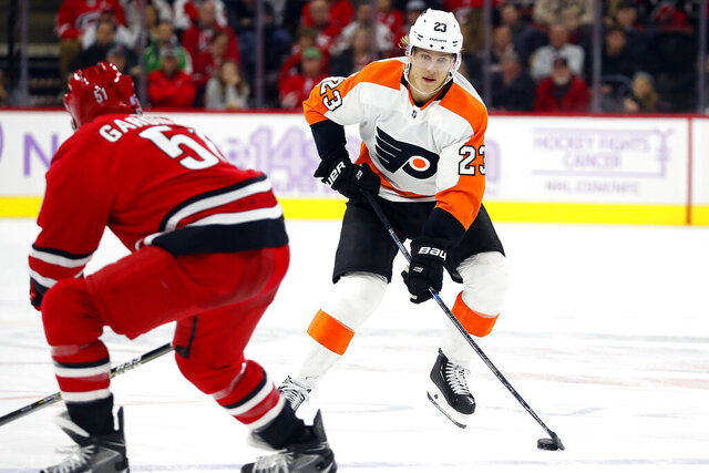 FILE - In this  Thursday, Nov. 21, 2019 file photo, Philadelphia Flyers' Oskar Lindblom (23) moves the puck against Carolina Hurricanes' Jake Gardiner (51) during the third period of an NHL hockey game in Raleigh, N.C. Philadelphia Flyers forward Oskar Lindblom has completed radiation treatments for a rare form of bone cancer.  He rang the bell at Abramson Cancer Center at Pennsylvania Hospital, which signifies that he has completed his radiation treatments. The 23-year-old Lindblom was diagnosed in December with Ewing's sarcoma, a cancerous tumor that grows in the bones or in the tissue around bones.  Lindblom says he's grateful the cancer was caught early and he's happy to be alive. (AP Photo/Karl B DeBlaker, File)