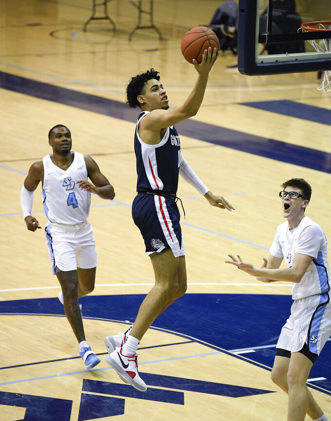 Gonzaga guard Julian Strawther (0) shoots past San Diego forward Josh Parrish (4) and guard Finn Sullivan (5) during the first half of an NCAA college basketball game Thursday, Jan. 28, 2021, in San Diego. (AP Photo/Denis Poroy)