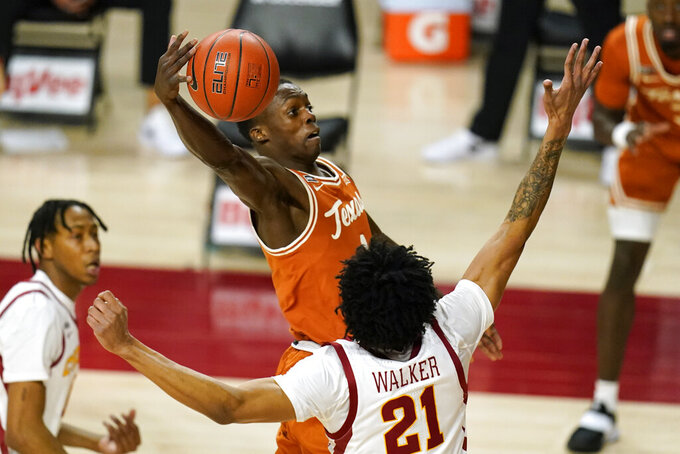 Texas guard Andrew Jones drives to the basket over Iowa State guard Jaden Walker (21) during the first half of an NCAA college basketball game, Tuesday, March 2, 2021, in Ames, Iowa. (AP Photo/Charlie Neibergall)