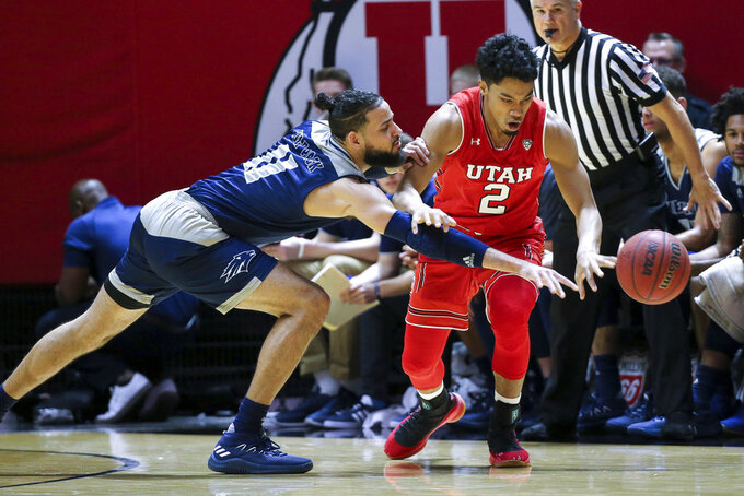 Nevada forward Cody Martin (11) tries to steal the ball from Utah guard Sedrick Barefield (2) during the first half of an NCAA college basketball game, Saturday, Dec. 29, 2018, in Salt Lake City. (AP Photo/Chris Nicoll)