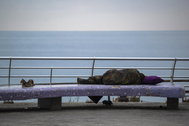 FILE - In this, July 19, 2020 file photo, a homeless woman sleeps on a bench on the Mediterranean Sea corniche in Beirut, Lebanon. The World Bank has approved a $246 million loan to Lebanon to provide emergency cash assistance to nearly 800,000 Lebanese reeling under the country's compounded economic and health crises. The World Bank said in a statement late Tuesday, Jan. 12, 2021, that the loan would also support the development of a national social safety net in Lebanon. (AP Photo/Hassan Ammar, File)