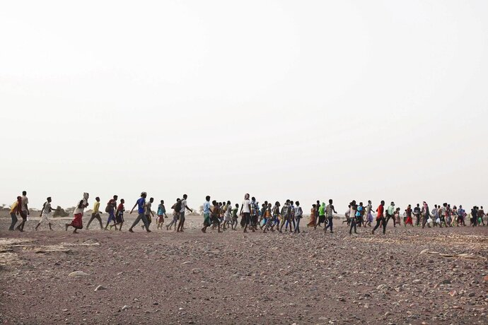 In this July 14, 2019 photo, smugglers lead Ethiopian migrants in Obock, Djibouti. The flow of migrants taking this route has grown. According to the U.N.'s International Organization for Migration, 150,000 arrived in Yemen from the Horn of Africa in 2018, a 50% jump from the year before. The number in 2019 was similar. They dream of reaching Saudi Arabia, and earning enough to escape poverty by working as laborers, housekeepers, servants, construction workers and drivers. (AP Photo/Nariman El-Mofty)