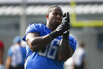 Detroit Lions defensive tackle Mike Daniels puts on gloves during NFL football practice in Allen Park, Mich., Sunday, July 28, 2019. (AP Photo/Paul Sancya)