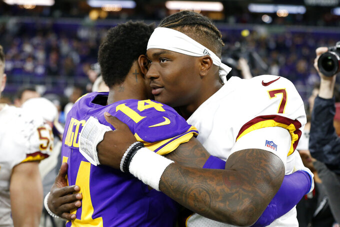 Washington Redskins quarterback Dwayne Haskins (7) hugs Minnesota Vikings wide receiver Stefon Diggs (14) after an NFL football game, Thursday, Oct. 24, 2019, in Minneapolis. The Vikings won 19-9. (AP Photo/Jim Mone)