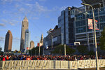 Football fans watch from outside the NFL Draft Theatre during the second round of the NFL football draft, Friday, April 30, 2021, in Cleveland. (AP Photo/David Dermer)