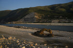 In this June 23, 2019 photo, an abandoned bulldozer sits on the banks of the Vjosa River at the construction site of the Kalivac dam in Albania. Some tout hydropower as a reliable, cheap and renewable energy source that helps curb dependence on planet-warming fossil fuels like coal, oil and natural gas. But some critics like EcoAlbania say the benefits of hydropower are overstated _ and outweighed by the harm dams can do. (AP Photo/Felipe Dana)