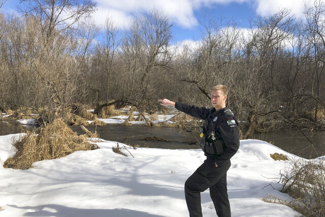 In this March 5, 2020 photo, Wisconsin Department of Natural Resources Warden Austin Schumacher stands on the edge of a marsh in Edgerton, Wis., where a 13-year-old boy disappeared after running away from school in November 2019. Schumacher used old-school tracking skills to find and rescue the child moments before a snowstorm struck. This month, Schumacher received the DNR's Lifesaving Award.  (AP Photo/Todd Richmond)