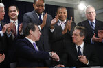 FILE - In this Thursday, Jan. 24, 2019, file photo, New York Gov. Andrew Cuomo, left, and actor Ben Stiller shake hands after the governor signed a bill into law to allow for early voting, in New York. The bill will allow New Yorkers to cast a ballot before Election Day in a bid to improve its low voter turnout rates. Stiller had lobbied for the new law. An effort by Democrats to implement broad reforms to the nation's voting process has stalled in the U.S. Senate, but some states, such as New York, are moving forward to expand access through early voting, same-day voter registration and other measures ahead of 2020. (AP Photo/Mark Lennihan, File)