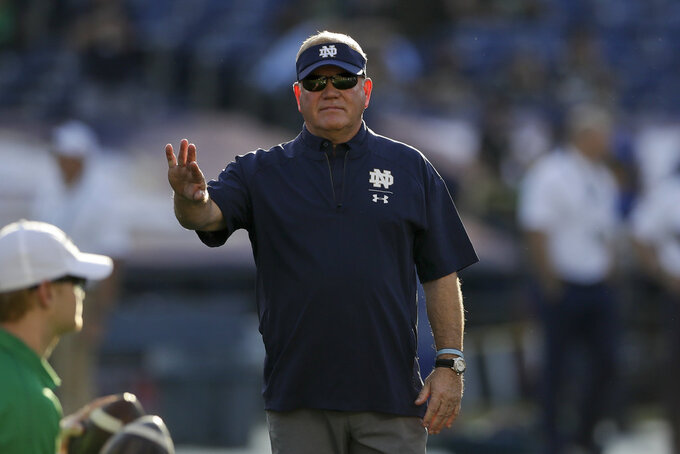 Notre Dame head coach Brian Kelly watches as his team warms up before facing Navy in an NCAA college football game Saturday, Oct. 27, 2018, in San Diego. (AP Photo/Gregory Bull)