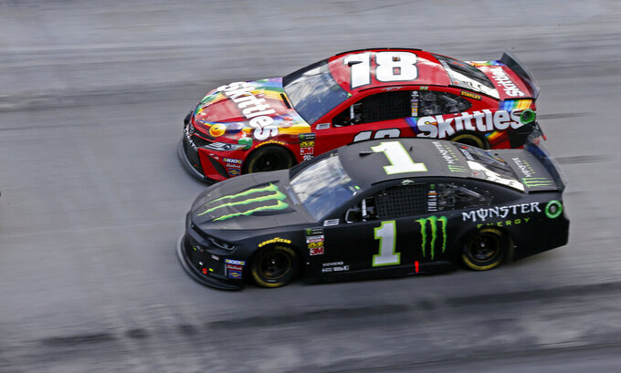 Kyle Busch (18)  drives next to his brother Kurt Busch (1) on a restart during a NASCAR Cup Series auto race, Sunday, April 7, 2019, in Bristol, Tenn. (AP Photo/Wade Payne)