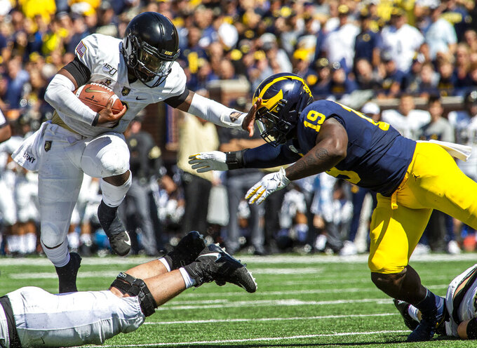 Army quarterback Kelvin Hopkins Jr. (8) leaps over his guard with pressure from Michigan defensive lineman Kwity Paye (19) in the second quarter of an NCAA football game in Ann Arbor, Mich., Saturday, Sept. 7, 2019. (AP Photo/Tony Ding)