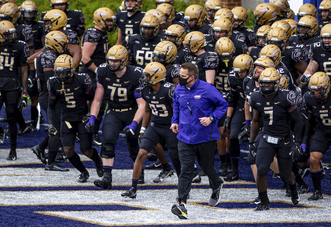 James Madison head coach Curt Cignetti leads his team onto the field for an an NCAA college football game against Richmond in Harrisonburg, Va., Saturday, April 17, 2021. (Daniel Lin/Daily News-Record Via AP)