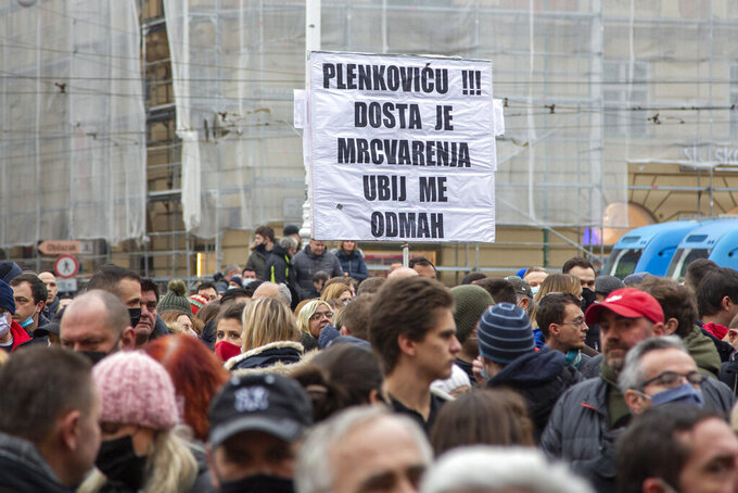 """Several thousand owners of restaurants, bars and other businesses that have been shut down during the coronavirus pandemic rally against government measures in Zagreb, Croatia, Wednesday, Feb. 3, 2021. The protests was organized by an association of entrepreneurs who are demanding that they be allowed to work while respecting the coronavirus safety rules. The placard reads: """"Plenkovic, (prime minister) it is enough of scarifying us, kill us immediately."""" (AP Photo/Darko Bandic)"""