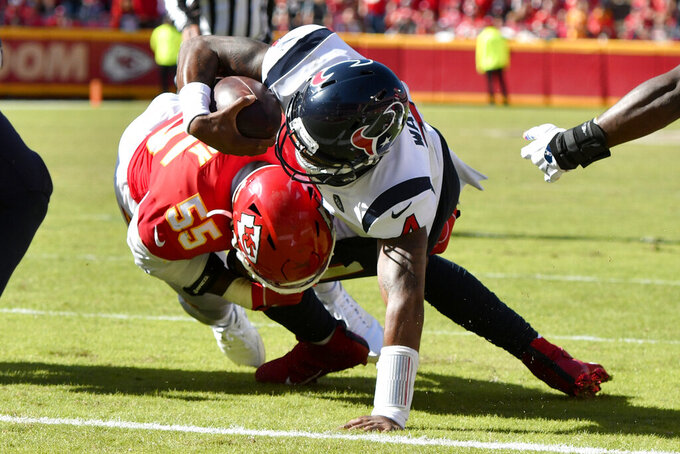 Houston Texans quarterback Deshaun Watson (4) scores a touchdown against Kansas City Chiefs defensive end Frank Clark (55) during the second half of an NFL football game in Kansas City, Mo., Sunday, Oct. 13, 2019. (AP Photo/Ed Zurga)