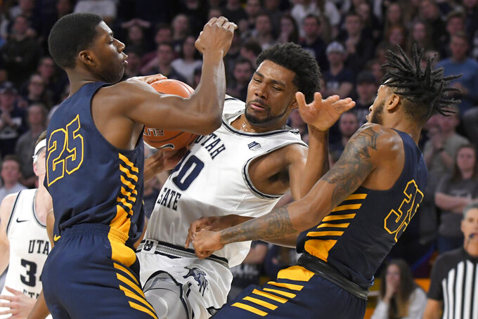 Utah State forward Alphonso Anderson (10) drives to the basket as North Carolina A&T forwards Webster Filmore (25) and Tyrone Lyons (35) defend during the second half of an NCAA college basketball game Friday, Nov. 15, 2019, in Logan, Utah. (AP Photo/Eli Lucero)