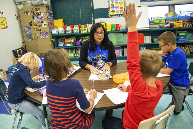 In this Nov. 24, 2019, photo first grade teacher Niva Vargo works with her students on a reading activity at David Leech Elementary in Leechburg, Pa. (Pittsburgh Post-Gazette via AP)