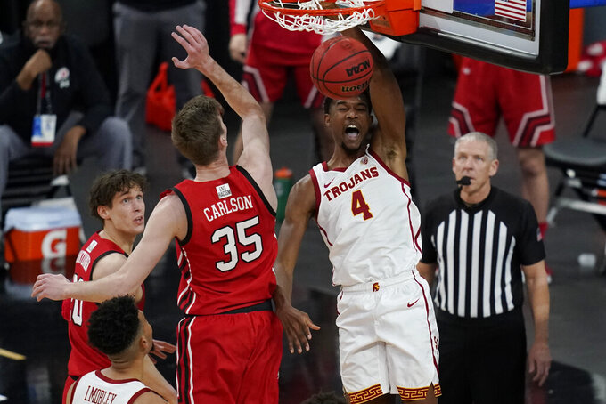 Southern California's Evan Mobley (4) dunks against Utah's Branden Carlson (35) during the first half of an NCAA college basketball game in the quarterfinal round of the Pac-12 men's tournament Thursday, March 11, 2021, in Las Vegas. (AP Photo/John Locher)