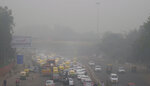 In this Sunday, Nov. 3, 2019, photo, vehicles wait for a signal at a crossing as the city enveloped in smog in New Delhi, India. Authorities in New Delhi are restricting the use of private vehicles on the roads under an