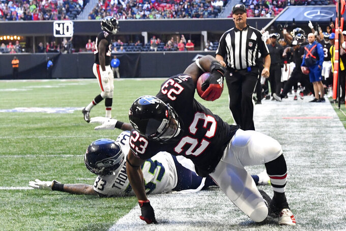 Atlanta Falcons running back Brian Hill (23) scores a touchdown against Seattle Seahawks free safety Tedric Thompson (33) during the second half of an NFL football game, Sunday, Oct. 27, 2019, in Atlanta. (AP Photo/John Amis)