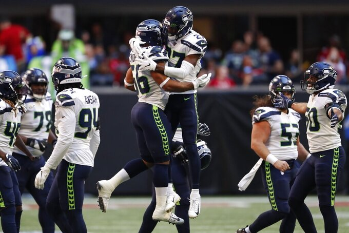 Seattle Seahawks linebacker Mychal Kendricks (56) and Seattle Seahawks defensive back Marquise Blair (27) celebrate a turnover against the Atlanta Falcons during the first half of an NFL football game, Sunday, Oct. 27, 2019, in Atlanta. (AP Photo/John Bazemore)