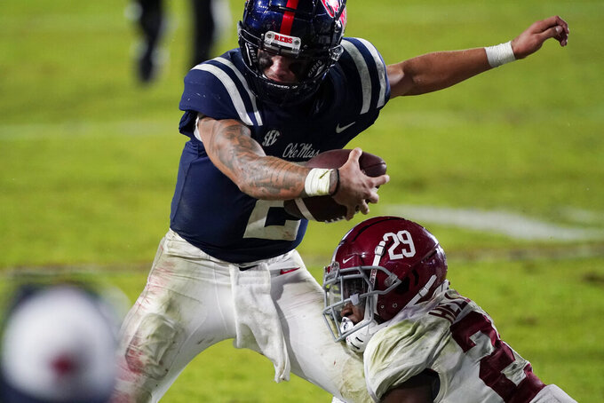 Mississippi quarterback Matt Corral (2) is tackled by Alabama defensive back DeMarcco Hellams (29) during the second half of an NCAA college football game in Oxford, Miss., Saturday, Oct. 10, 2020. Alabama won 63-48. (AP Photo/Rogelio V. Solis)