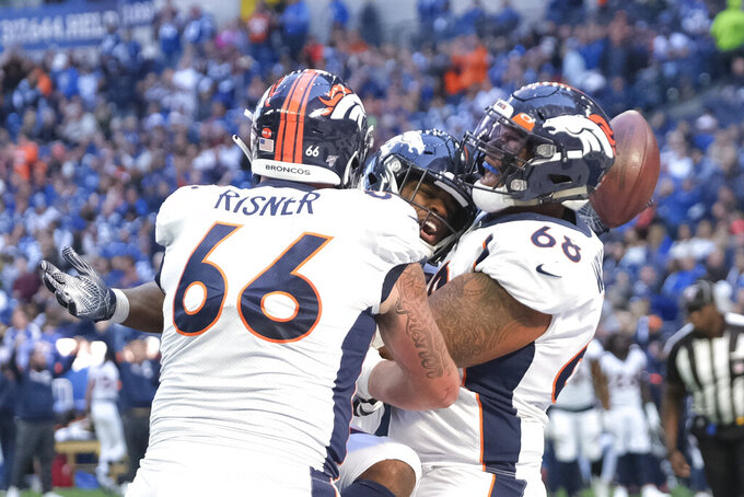 Denver Broncos' Royce Freeman celebrates a touchdown with Dalton Risner (66) and Elijah Wilkinson (68) during the second half of an NFL football game, Sunday, Oct. 27, 2019, in Indianapolis. (AP Photo/AJ Mast)