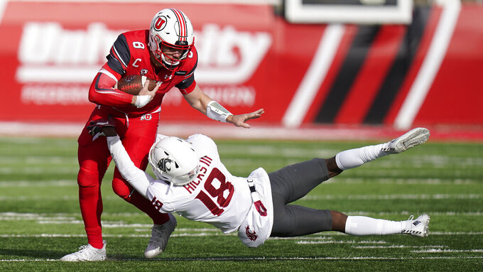 Washington State defensive back George Hicks III (18) tackles Utah quarterback Jake Bentley (8) during the first half of an NCAA college football game Saturday, Dec. 19, 2020, in Salt Lake City. (AP Photo/Rick Bowmer)