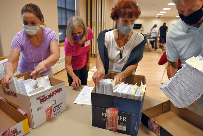 FILE - In this Aug. 11, 2020, file photo, volunteers sort mail-in ballots on Primary Day, in Glastonbury, Conn. Town and city clerks across Connecticut have been enlisting volunteers, hiring extra staff and paying overtime to workers to process an unprecedented number of requests for absentee election ballots. (AP Photo/Jessica Hill, File)