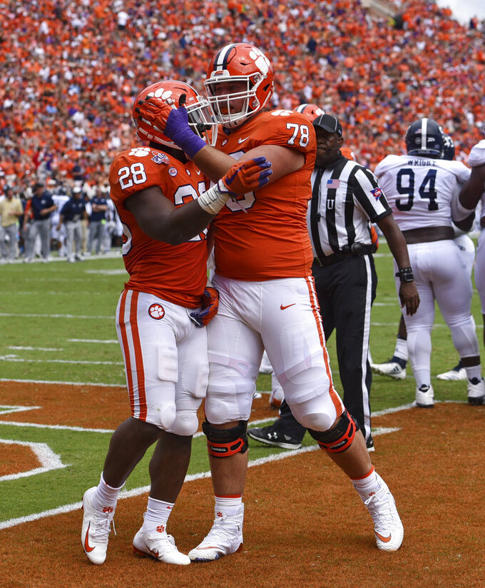 Clemson's Tavien Feaster (28) celebrates his touchdown with Chandler Reeves during the first half of an NCAA college football game against Georgia Southern, Saturday, Sept. 15, 2018, in Clemson, S.C. (AP Photo/Richard Shiro)