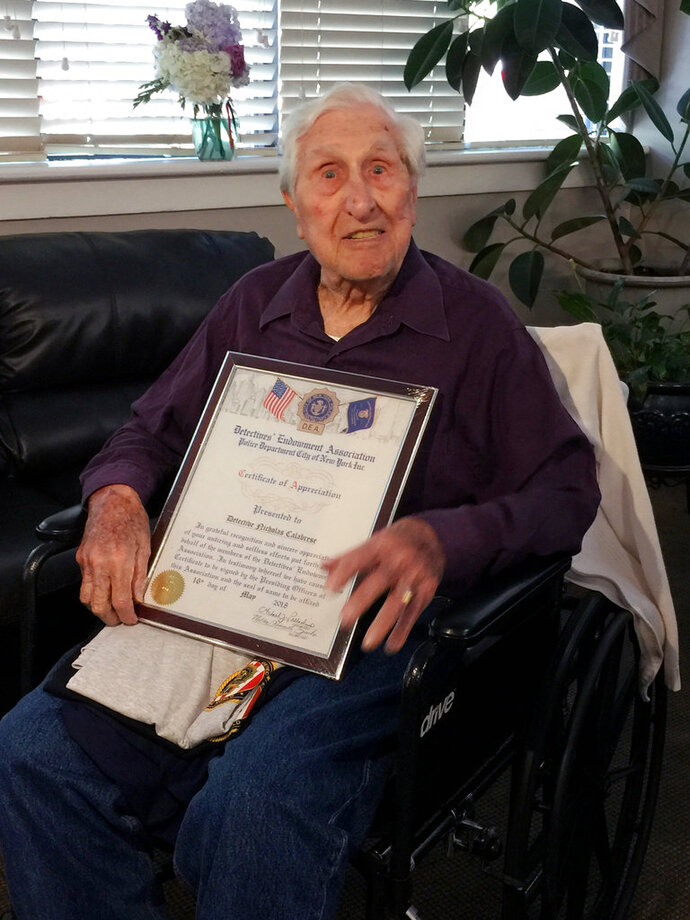 In this photo provided by The Detectives' Endowment Association, retired New York Police Department detective Nicholas Calabrese holds a framed certificate from The Detectives' Endowment Association honoring him as their oldest living retired detective, Tuesday, May 15, 2018, in the Bronx borough of New York. Calabrese, who is 101-years-old, originally joined the force in 1953. (Sam Katz/The Detectives' Endowment Association via AP)