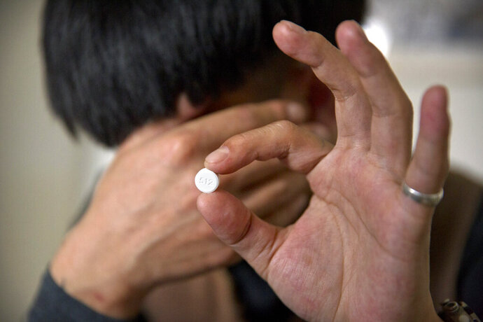 In this March 28, 2019, photo, Yin Hao, who also goes by Yin Qiang, holds a Tylox pill while sitting in a tea house in Xi'an, northwestern China's Shaanxi Province. Officially, pain pill abuse is an American problem, not a Chinese one. But people in China have fallen into opioid abuse the same way many Americans did, through a doctor's prescription. And despite China's strict regulations, online trafficking networks, which facilitated the spread of opioids in the U.S., also exist in China. (AP Photo/Mark Schiefelbein)