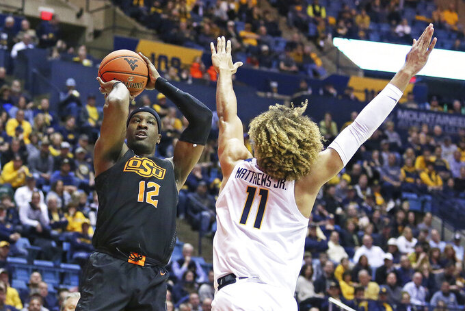 Oklahoma State forward Cameron McGriff (12) shoots as West Virginia forward Emmitt Matthews Jr. (11) defends during the first half of an NCAA college basketball game Tuesday, Feb. 18, 2020, in Morgantown, W.Va. (AP Photo/Kathleen Batten)