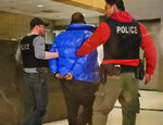 In this still image taken from video, R. Kelly is escorted by police in custody at the Chicago Police Department's Central District Friday night, Feb. 22, 2019, in Chicago. R&B star Kelly arrived Friday night at a Chicago police precinct, hours after authorities announced multiple charges of aggravated sexual abuse involving four victims, including at least three between the ages of 13 and 17. (Nader Issa/Chicago Sun-Times via AP)