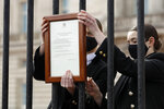 Members of staff attach an announcement, regarding the death of Britain's Prince Philip, to the fence of Buckingham Palace in London, Friday, April 9, 2021. Buckingham Palace officials say Prince Philip, the husband of Queen Elizabeth II, has died. He was 99. Philip spent a month in hospital earlier this year before being released on March 16 to return to Windsor Castle. (AP Photo/Matt Dunham)