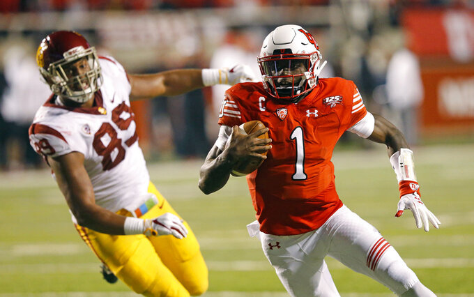Utah quarterback Tyler Huntley (1) carries the ball in for a touchdown as Southern California defensive lineman Christian Rector (89) pursues during the first half of an NCAA college football game Saturday, Oct. 20, 2018, in Salt Lake City. (AP Photo/Rick Bowmer)