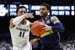 Marquette's Markus Howard, right, drives against Xavier's Bryce Moore (11) during the first half of an NCAA college basketball game Wednesday, Jan. 29, 2020, in Cincinnati. (AP Photo/John Minchillo)