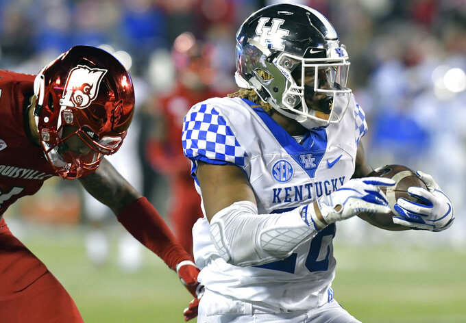 Kentucky running back Benny Snell Jr. (26) runs from the grasp of Louisville safety TreSean Smith (4) as he scores a touchdown during the first half of an NCAA college football game in Louisville, Ky., Saturday, Nov. 24, 2018. (AP Photo/Timothy D. Easley)