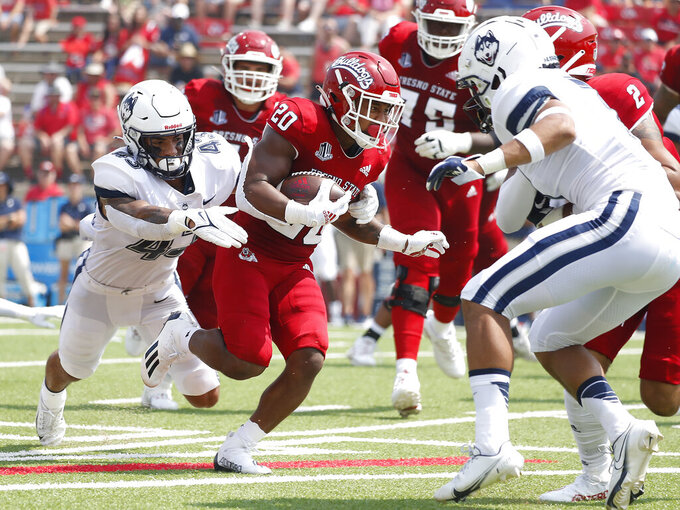 Fresno State running back Ronnie Rivers (20) is chased by Connecticut linebacker Jackson Mitchell, left, during the first half of an NCAA college football game in Fresno, Calif., Saturday, Aug. 28, 2021. (AP Photo/Gary Kazanjian)