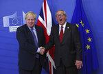 British Prime Minister Boris Johnson shakes hands with European Commission President Jean-Claude Juncker during a press point at EU headquarters in Brussels, Thursday, Oct. 17, 2019. Britain and the European Union reached a new tentative Brexit deal on Thursday, hoping to finally escape the acrimony, divisions and frustration of their three-year divorce battle. (AP Photo/Francisco Seco)