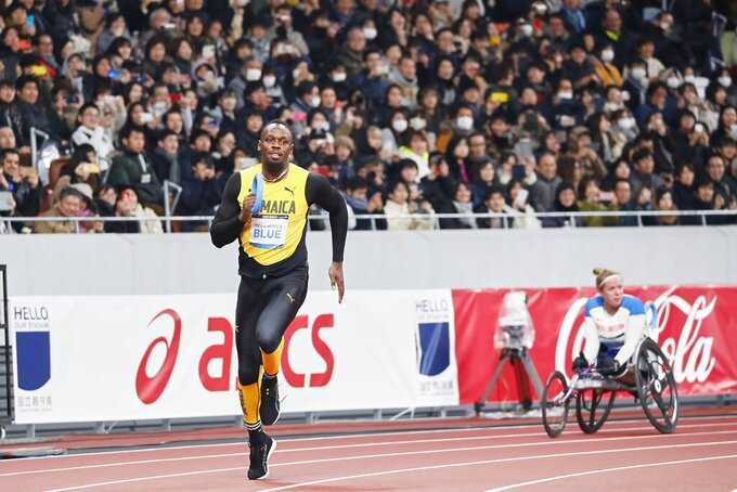 In this photo provided by Japan Sports Council (JSC), Olympics gold medalist Usain Bolt, left, of Jamaica runs at the opening ceremony of the New National Stadium, the main venue for the Tokyo 2020 Olympic and Paralympic Games, in Tokyo, Japan, Saturday, Dec. 21, 2019. (JSC via AP)