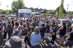 Hundreds of activists gather around two unmarked buses outside the Crane Shed Commons on Wednesday, Aug. 12, 2020, in Bend, Ore.  Protesters rallied to block Immigration and Customs Enforcement officials from detaining two men.  (Ryan Brennecke/The Bulletin via AP)
