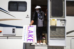 In this Friday, June 19, 2020, photo Jeannine Lee Lake, Democratic candidate for Indiana's 6th congressional district, passes out yard signs from her motorhome during a Juneteenth day event in Columbus, Ind. Lake never would have imagined when she first ran against Greg Pence, Vice President Mike Pence's brother, for a rural Indiana congressional seat two years ago: An almost entirely white crowd of more than 100 people marching silently in the Pences' hometown, sending up prayers for Black people killed by police and an end to systemic racism.  (AP Photo/Michael Conroy)