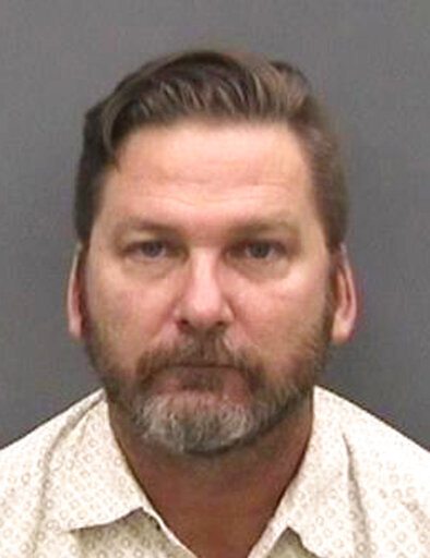 FILE - This photo made available by the Hillsborough County Sheriff's Office, in Florida, shows Mark William Ackett under arrest, Wednesday, Sept. 12, 2018. Ackett, a former Florida teacher, was convicted Thursday, April 1, 2021, of secretly recording 124 students and an adult teacher undressing over a period of nearly two years. (Hillsborough County Sheriff's Office via AP, File)